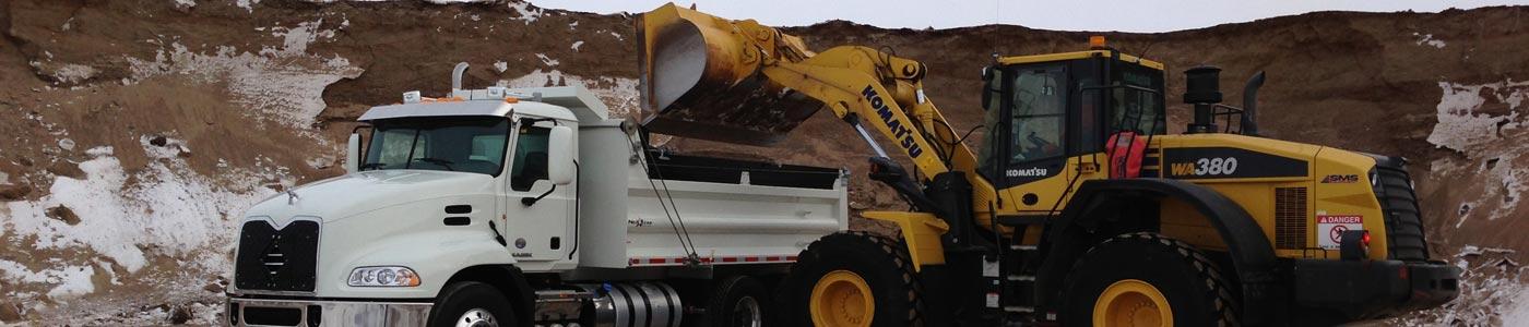 backhoe filling dump truck with sand